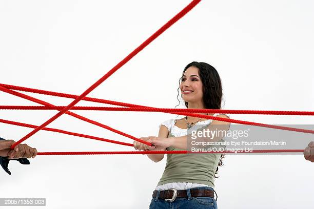 People pulling red rope