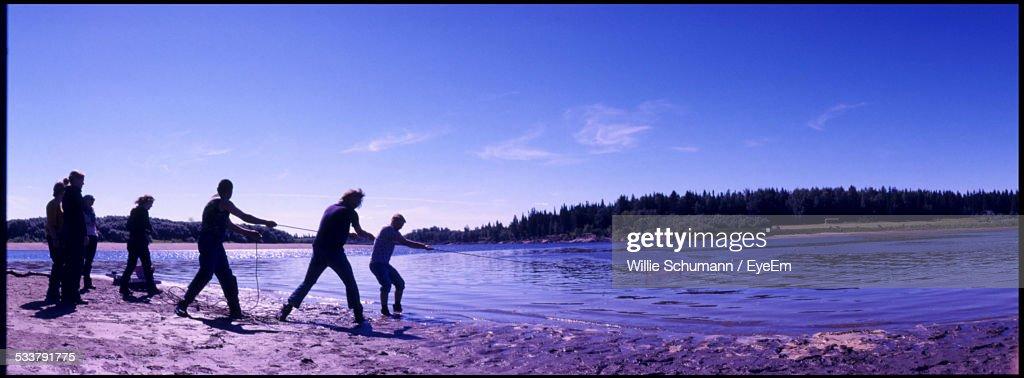 People Pulling Rope From Lake Using Strength : Foto stock