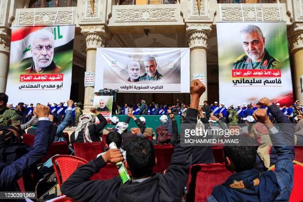 People pump their fists beneath a portrait of slain Iranian Revolutionary Guards commander Qasem Soleimani and Abu Mahdi al-Muhandis - the deputy...