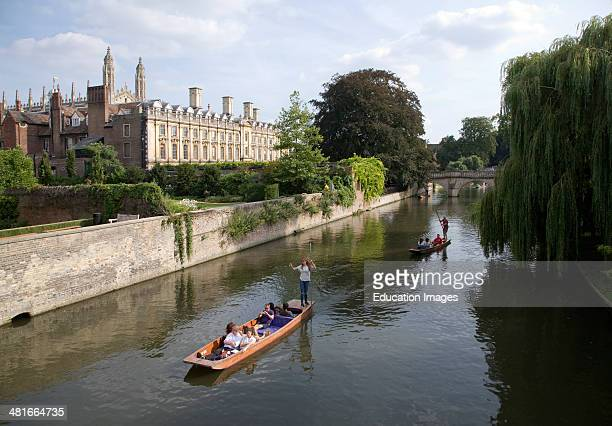 People punting in small boats on the River Cam Cambridge England with Clare College in the background