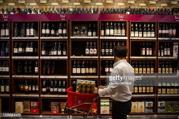 People purchase alcohol at a Big C supermarket the night before a citywide alcohol ban on April 9, 2020 in Bangkok, Thailand. Thai authorities have...