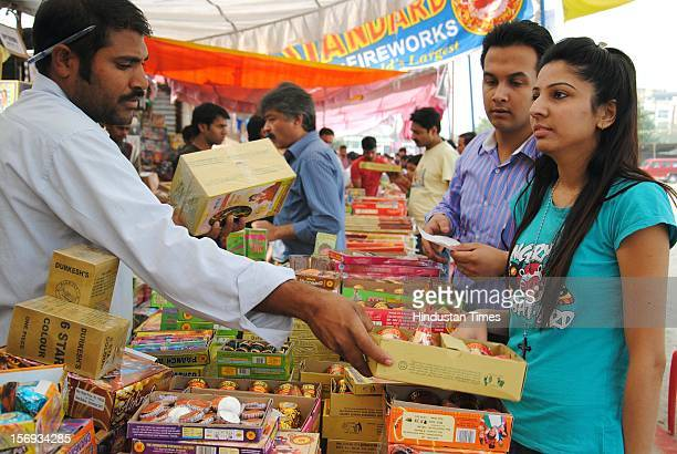 People purchase crackers on the eve of Diwali festival at a market, on November 11, 2012 in Noida, India.