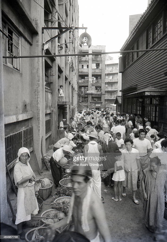 People purchase dailies at stalls at the Hashima on August 12, 1956 in Takashima, Nagasaki, Japan. The coal mining island, is also known as the Battleship Island, whose population used to be more than 5,000 in its heyday in 1959. In the residential area there were the Japan's first concrete building apartments.