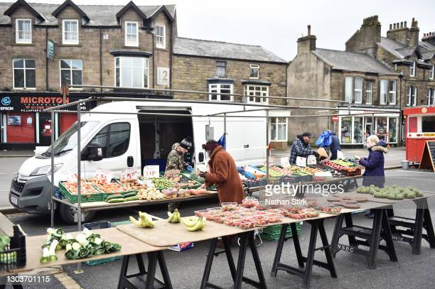 People purchase fruit and vegetables from a greengrocer market stall on February 23, 2021 in Buxton, England.
