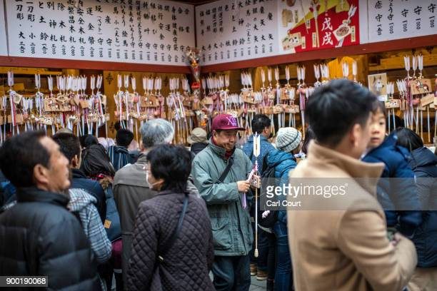 People purchase lucky charms know as 'omamori' after praying for the new year at Tsurugaoka Hachimangu Shinto shrine on January 1 2018 in Kamakura...