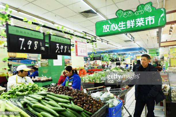 People purchase vegetables at a supermarket on January 10 2018 in Hangzhou Zhejiang Province of China China's consumer price index rose 18 percent...