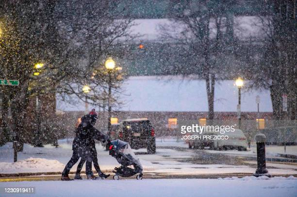People push a baby carriage through the Navy Yard in heavy snow fall during winter storm Orlena in Boston, Massachusetts on February 1, 2021. - The...