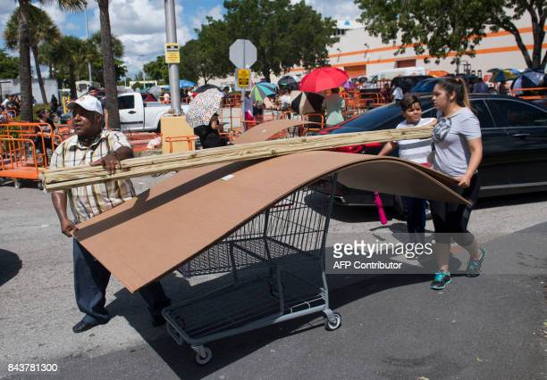People push a cart full of wood and supplies outside a Home Depot store in Miami Florida as they prepare for Hurricane Irma on September 7 2017 Miami...