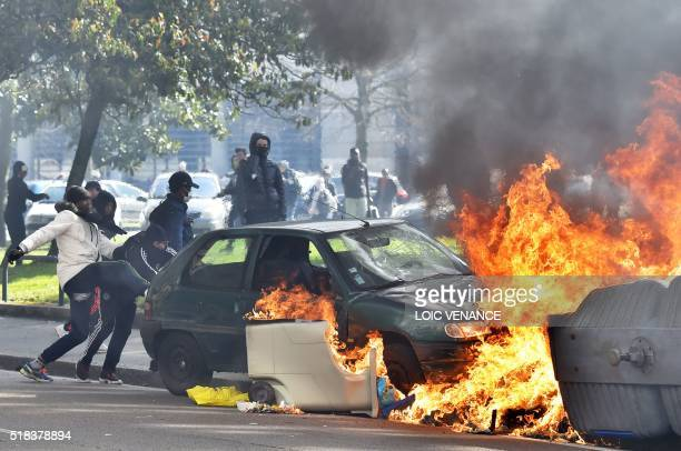 TOPSHOT People push a damaged car towards a garbage set on fire during a protest by unions and students on March 31 2016 in Nantes western France...