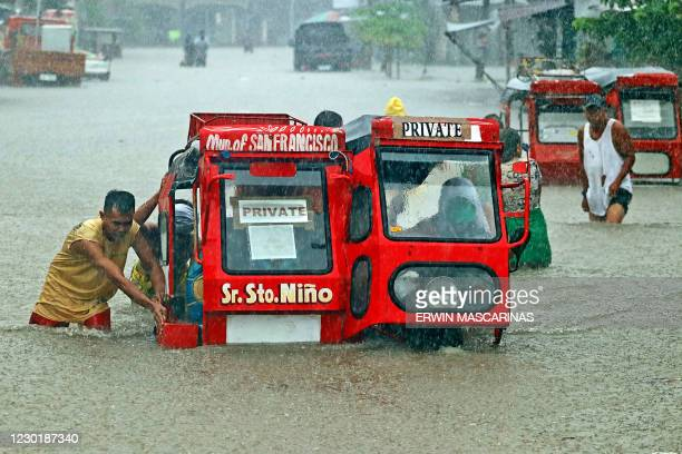 People push a half-submerged tricycle through a flooded street due to heavy rains caused by tropical depression Vicky in San Francisco town, Agusan...