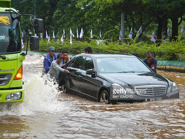 People push a Mercedes along a flooded road in Jakarta on February 10 2015 Heavy monsoon rains have flooded many sections of the Indonesian capital...