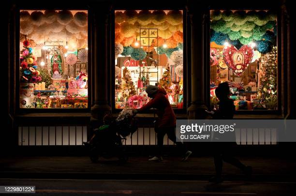 People push a pushchair past a festive, Christmas-themed window display of a shop in Manchester, northwest England, on November 26, 2020. - London...