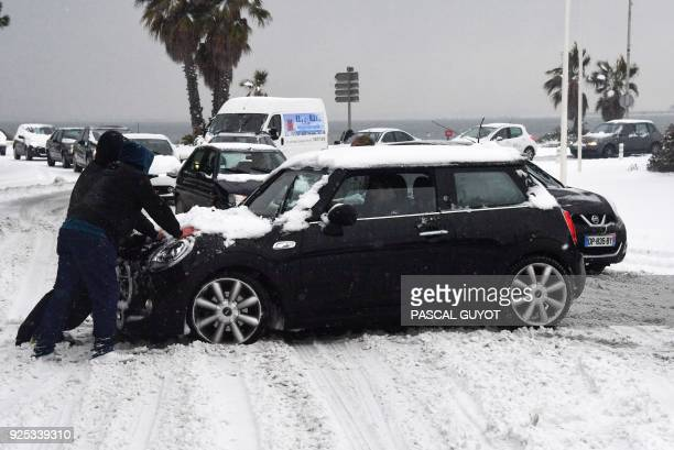 People push a vehicle on a snow covered road on February 28 in PalavaslesFlots southern France after heavy snow fall Europe remained on February 28...