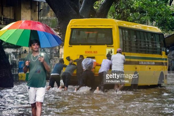 People push a vehicle through rain water near Dadar local railway station on July 9 2018 in Mumbai India Indias financial capital and its surrounding...