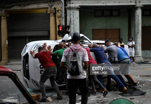 People push an overturned car in the street in the framework of a demonstration against Cuban President Miguel Diaz-Canel in Havana, on July 11,...