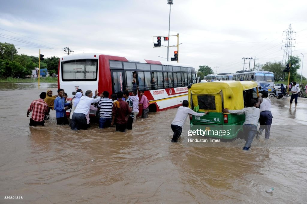 People push bus and auto-rickshaw as they broke down on waterlogged road at 45-50 light point due to rain on August 21 2017 in Chandigarh, India. Heavy rainfall on morning brought the tri-city (Chandigarh, Mohali, Panchkula) to a stand still as poor drainage system gave way to roads being flooded with water. The rainfall left the cars of commuters stuck in middle of the roads forcing them to leave their cars stranded.