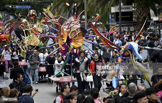People push floats with 'Alebrijes' along a street during the Ninth Monumental 'Alebrijes' Parade and contest on October 17 2015 in Mexico City Some...