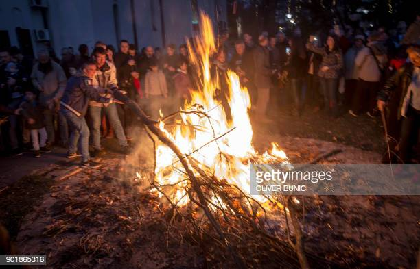 People push oak tree branches into a fire burning outside the Saint Sava church during the ceremonial burning of dried oak branches symbolising the...