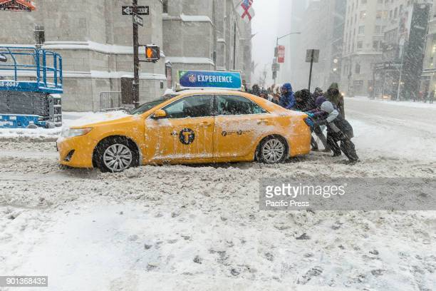 People push taxi stuck in snow in Manhattan under heavy snow storm cold and wind A giant winter bomb cyclone hit the US East Coast on Thursday with...