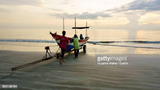 people pushing boat against sky during sunset - kuantan stock pictures, royalty-free photos & images