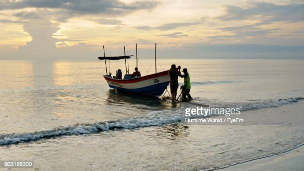 People Pushing Boat In Sea Against Sky During Sunset