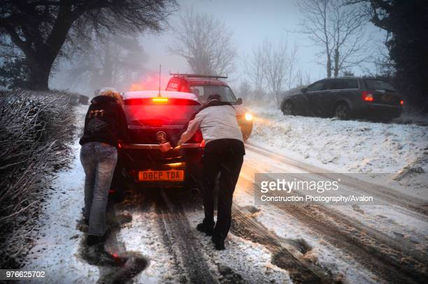 People pushing car stuck on snowy road UK