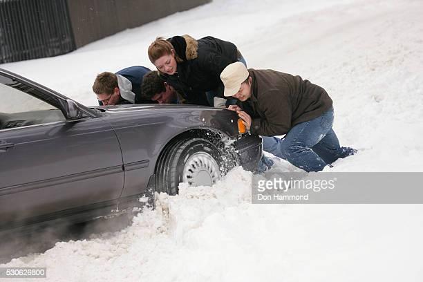 People Pushing Vehicle Stuck in Snow
