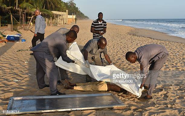 People put a blanket on a body lying on the beach following after gunmen went on a shooting rampage in the Ivory Coast resort of GrandBassam on March...
