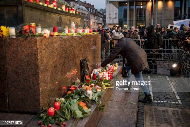 People put candles and flowers at the 'Brueder Grimm' monument after a vigil for the vicitms near the Midnight shisha bar one of the sites of last...