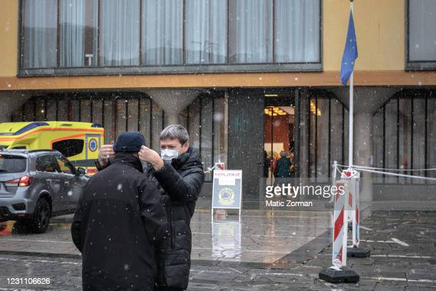 People put on the mandatory protective masks before they enter the vaccination centre on February 11, 2021 in Kranj, Slovenia. Slovenia plans to...