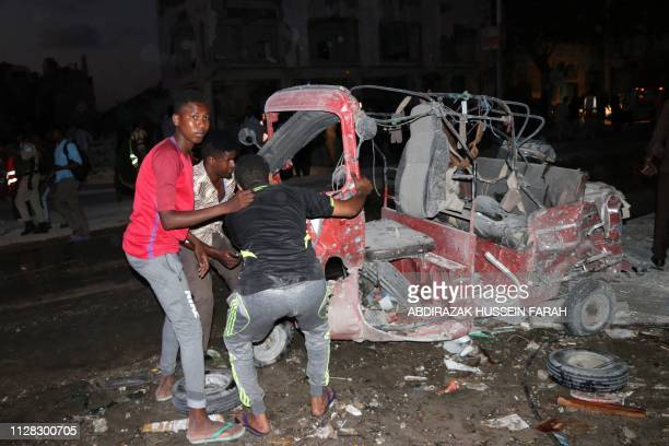 People put the wreckage of a vehicle on its wheels outside the Maka Al-Mukarama hotel in the Somalia capital, Mogadishu on March 1, 2019 after a car...