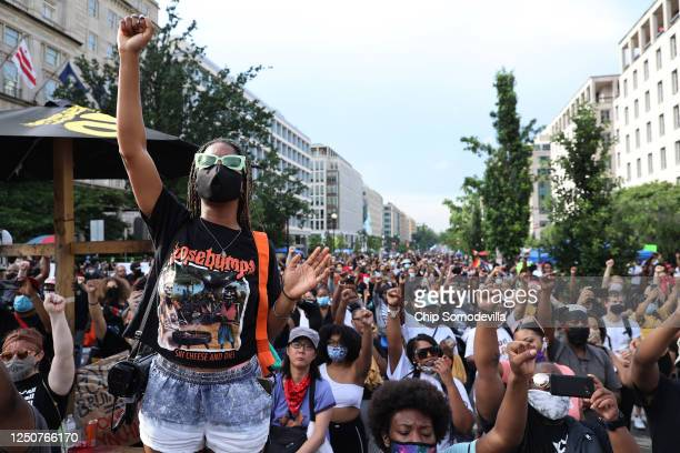 People put their fists in the air as Lift Every Voice and Sing is performed at the intersection of H St NW and 16th Street NW near the White House an...