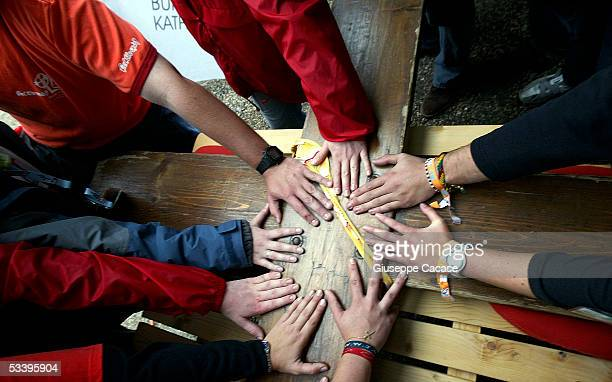 People put their hands on the Cross of the World Youth Day as it arrives in Cologne on August 16, 2005 in Cologne, Germany. Thousands of young...