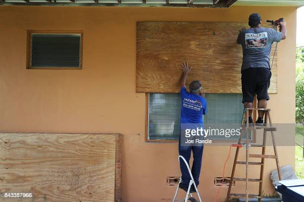 People put up shutters as they prepare a family members house for Hurricane Irma on September 6 2017 in Miami Florida It's still too early to know...