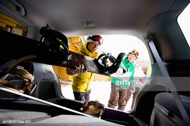 people putting snowboards into car trunk - wintersport stockfoto's en -beelden