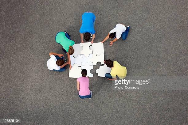 menschen zusammenzustellen puzzle - koordination stock-fotos und bilder