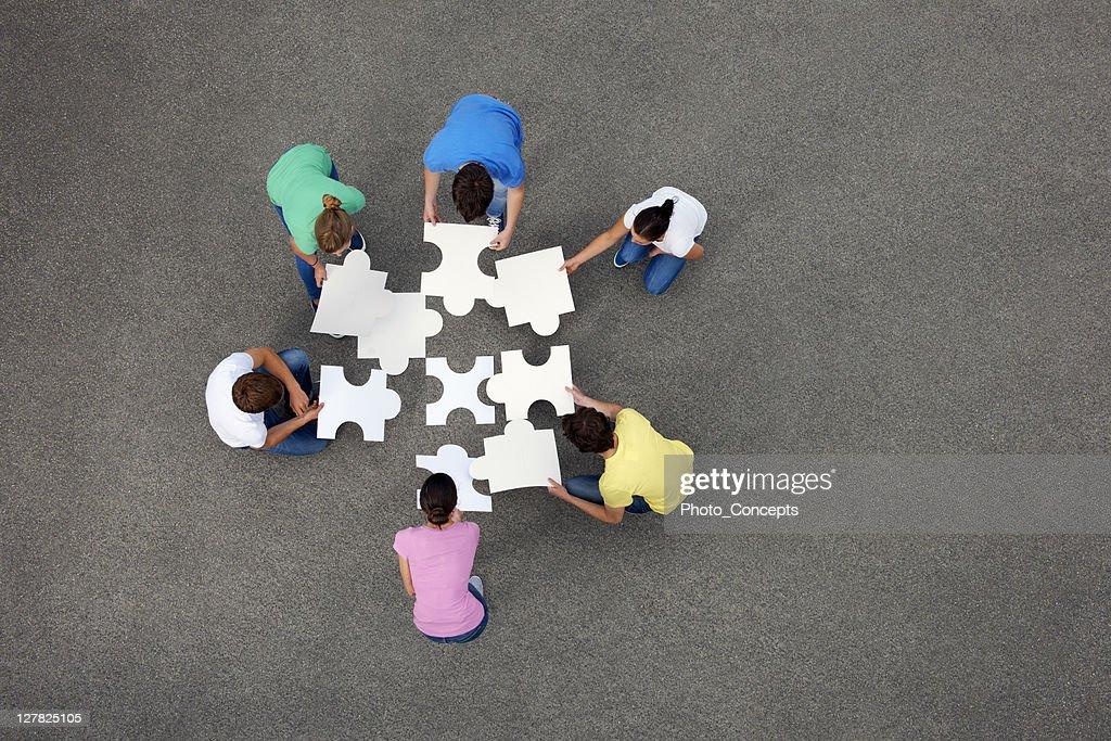 ジグソーパズルをはめる人々 : ストックフォト