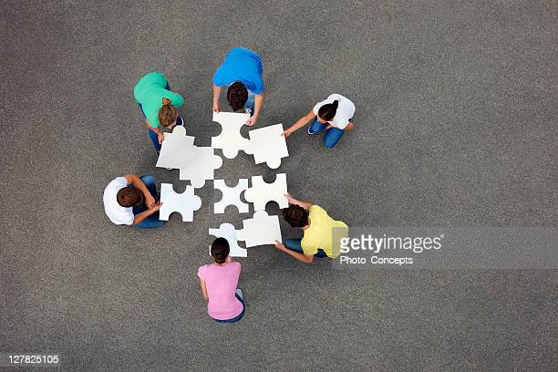 people putting together jigsaw puzzle - raadsel stockfoto's en -beelden