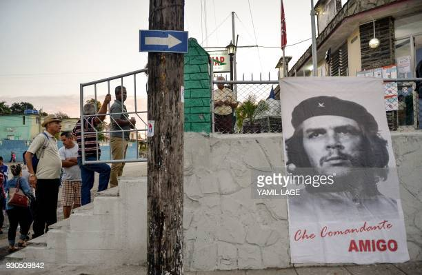 TOPSHOT People queue as a banner depicting revolutionary leader Ernesto 'Che' Guevara is seen at a polling station in Santa Clara Cuba during an...