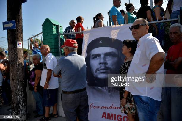 People queue as a banner depicting revolutionary leader Ernesto 'Che' Guevara is seen at a polling station in Santa Clara Cuba during an election to...