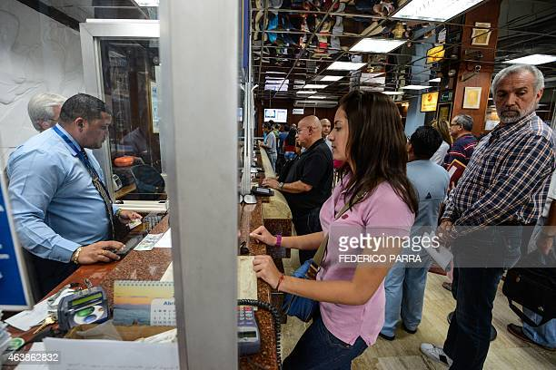 People queue at a currency exchange office in Caracas on February 19 2015 The Venezuelan bolivar opened Thursday at 172 to the dollar on the first...