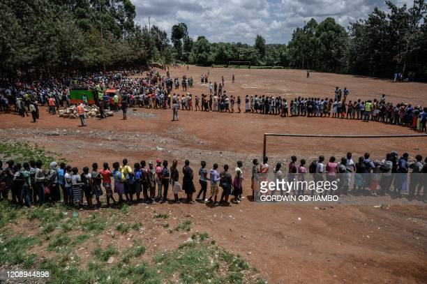 TOPSHOT People queue at a food distribution by Team Pangaj a Kenyan voluntary group delivering flour beans milk and juice for about 900 people at the...