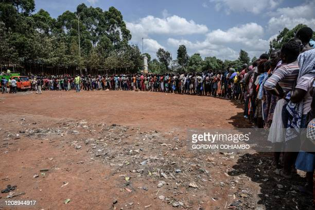 People queue at a food distribution by Team Pangaj a Kenyan voluntary group delivering flour beans milk and juice for about 900 people at the Olympic...