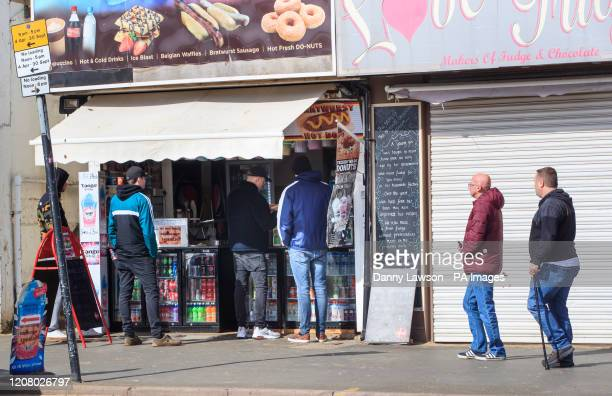 People queue at a kiosk selling food and drinks in the coastal town of Scarborough North Yorkshire as Prime Minister Boris Johnson has said the...