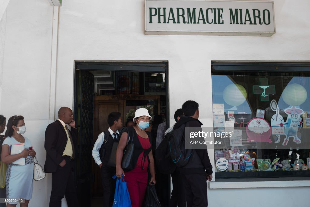 People queue at a pharmacy in downtown Antananarivo to buy protection masks against infections and medicines against plague on October 2, 2017. /