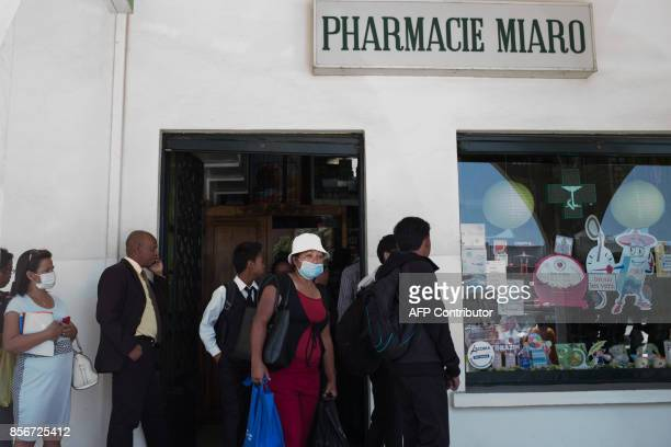People queue at a pharmacy in downtown Antananarivo to buy protection masks against infections and medicines against plague on October 2 2017 / AFP...