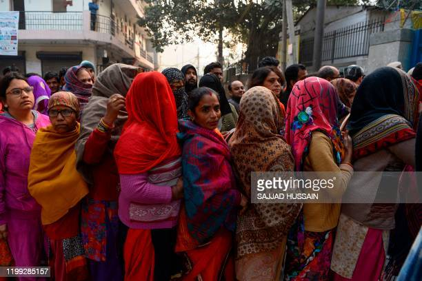 People queue at a polling station to cast their votes during the Legislative Assembly elections in New Delhi on February 8 2020