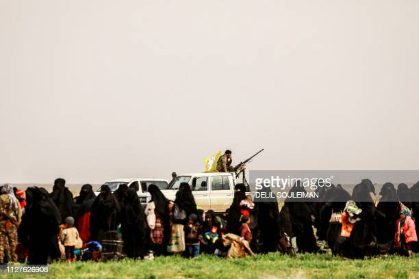 People queue at a scanning area for those who are evacuated from the Islamic State group's embattled holdout of Baghouz during an operation to expel...