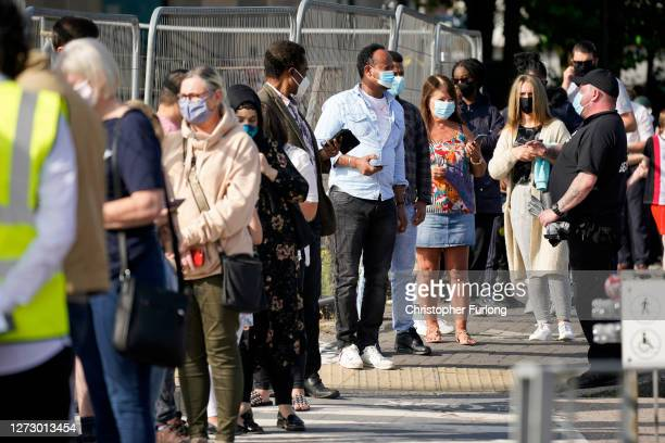 People queue at a walk in Covid-19 testing centre on September 17, 2020 in Bolton, England. Fears about rising infection rates among younger people...