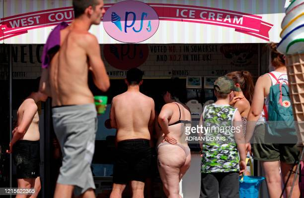 People queue at an Ice Cream shop near the beach in WestonsuperMare south west England on May 27 after lockdown measures were partially eased during...